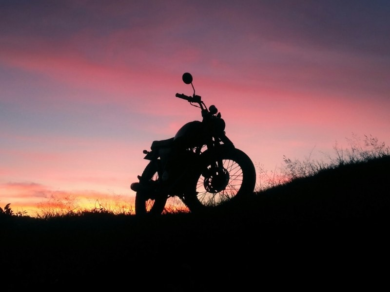 silhouette of a motorcycle in front of a night sky