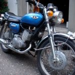 newly waxxed blue suzuki T250 motorcycle standing in the yard
